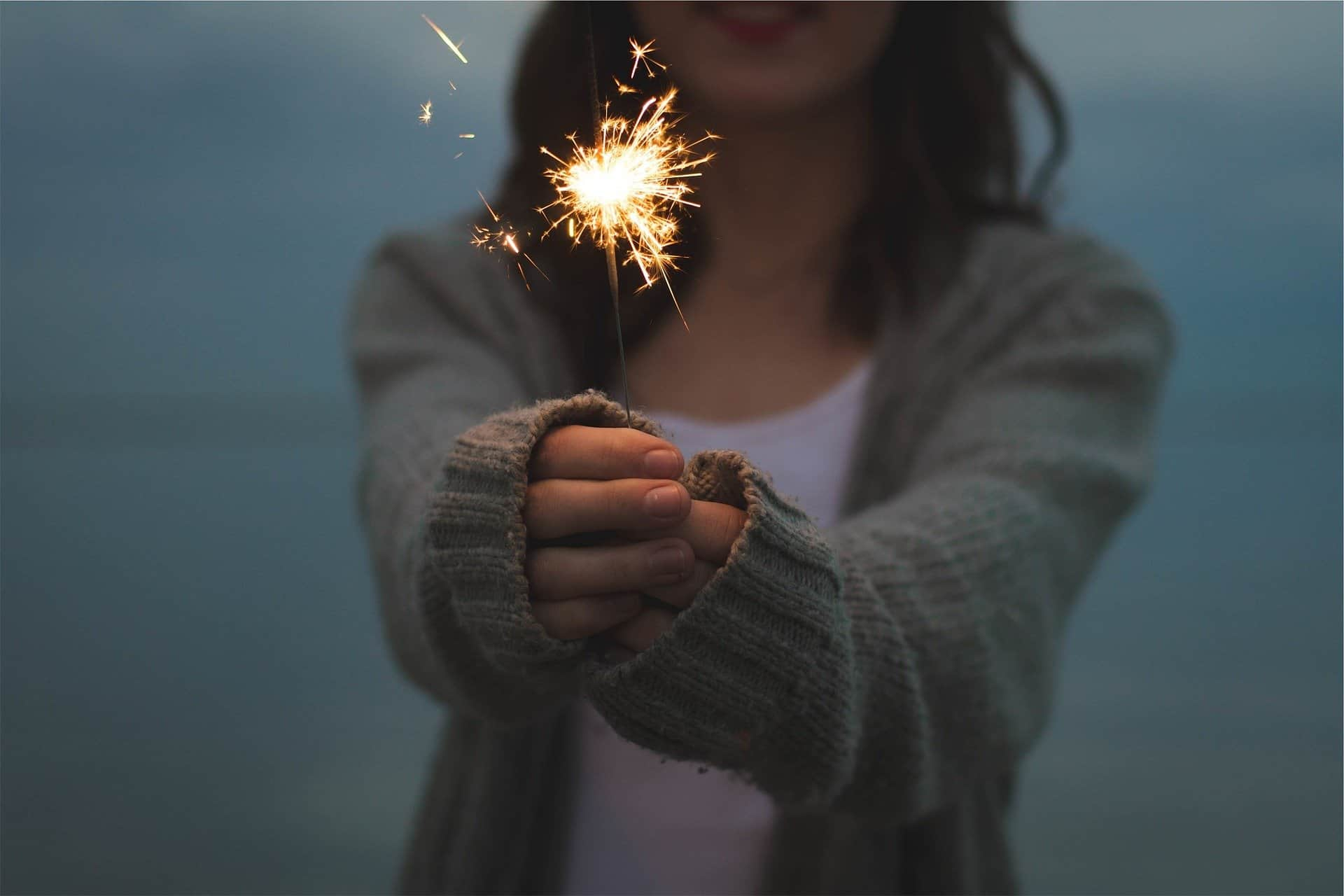 Woman holding a sparkler to celebrate a positive mindset in the new year